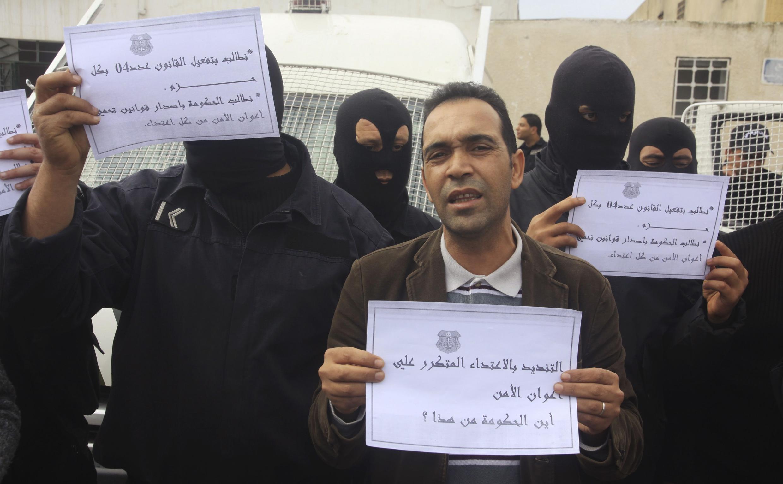 Des policiers brandissant des pancartes dénonçant l'attaque contre un poste de police à Douar Hicher près de Tunis, le 31 octobre 2012.
