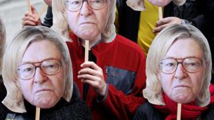 Manifestantes usam máscara do presidente honorário do partido Frente Nacional, Jean-Marie Le Pen, com o penteado da filha, a líder da extrema-direita, Marine Le Pen.