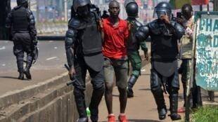 Maafisa wa polisi wa Guinea wakimkabili mmoja w waandamanaji, Novemba 14, 2019.