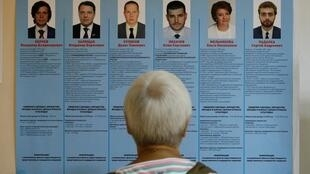 Eleitor frente ao cartaz dos candidatos em Moscovo 8/09/2019.