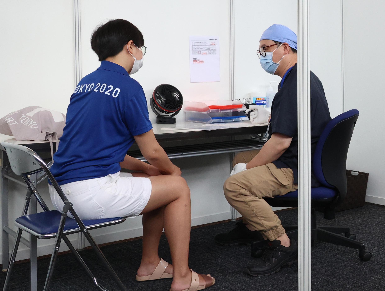 Uma mulher membro da organização dos Jogos Olímpicos passa por exames com um médico antes de ser vacinada contra a Covid-19, em Tóquio, 18 de junho de 2021.