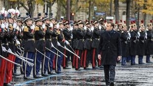 French President Emmanuel Macron reviews troops during a ceremony at the Arc de Triomphe in Paris as part of commemorations marking the 101st anniversary of the 1918 armistice, 11 November 2019.
