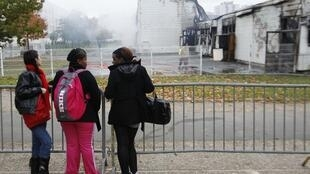 School children look at their burning school Val d'Huisne after it was destroyed by a fire in Le Mans