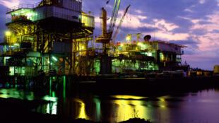 Oil production rig illuminated at dawn, Niger Delta, Nigeria