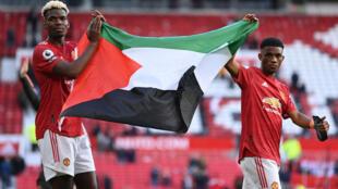 El francés Paul Pogba (izquierda) y el marfileño Amad Diallo (derecha) ondean una bandera palestina tras un partido de la Premier League en Manchester, el 18 de mayo de 2021