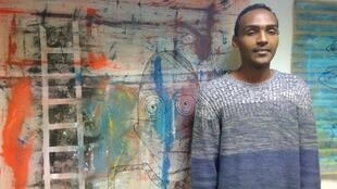 Mohammed Abdulatief stands with one of his paintings in his studio at the Atelier des Artistes en Exile in Paris.