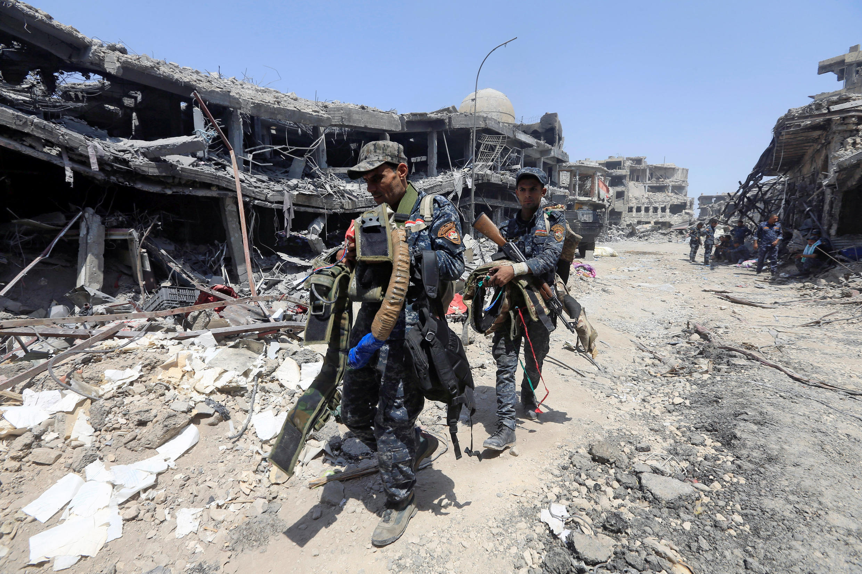 Membres des forces irakiennes portant une ceinture explosive utilisée par le groupe EI, le 9 juillet à Mossoul.