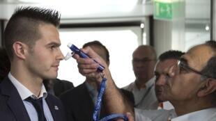 Médico Philippe Bargain faz uma demonstração do teste de temperatura praticado no aeroporto Charles de Gaulle.