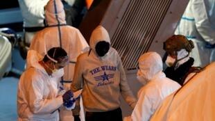 Des policiers maltais s'entretiennent avec des migrants débarquant d'un navire militaire qui est arrivé à Senglea dans le Grand Port de La Valette, à Malte le 10 avril 2020.