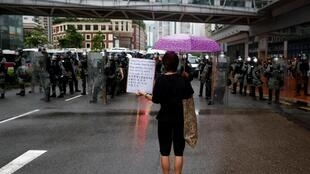 Un manifestant se tient devant la police antiémeute lors d'une manifestation à Hong Kong, le 25 août 2019.