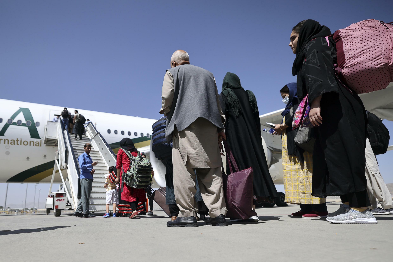 Los pasajeros se disponen a abordar un avión de la compañía paquistaní PIA, el primer vuelo comercial internacional en aterrizar y despegar del aeropuerto de Kabul, el 13 de septiembre de 2021 en la capital afgna