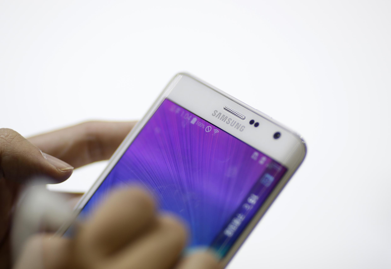 Ảnh minh họa : Một khách hàng thử điện thoại thông minh Galaxy của Samsung. Ảnh chụp nhân triễn lãm điện tử  2014 tại Goyang, Hàn Quốc.