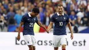Loïc Rémy (à gauche) et Karim Benzema se prennent par la main lors de la rentrée de l'équipe de France de football, face à l'Espagne.