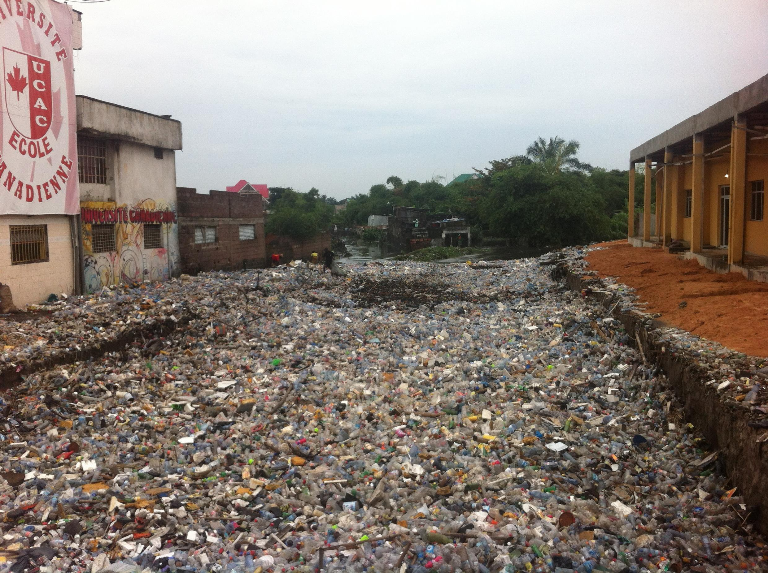 A riverbed in Limete, Kinshasa, DRC, polluted by plastic bottles and other plastic debris.