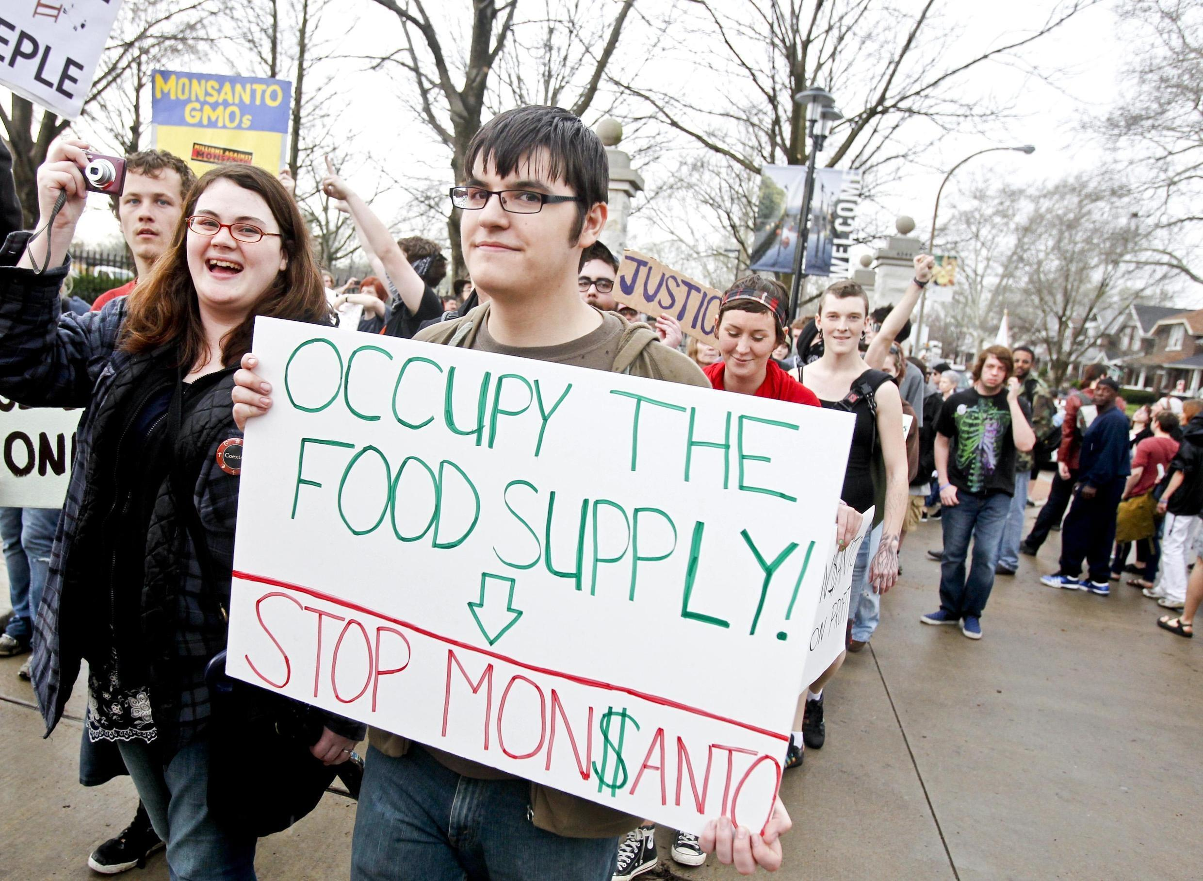 """Members of """"Occupy"""" movements in the Midwest protest against Monsanto's agricultural practices in front of the Missouri Botanical Garden during the """"Occupy the Midwest"""" regional conference in St. Louis, Missouri March 16, 2012."""