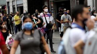 Les gens marchent dans une rue animée après que le gouvernement du président Nicolas Maduro a décidé d'assouplir le verrouillage en raison de la maladie des coronavirus (COVID-19), à Caracas, Venezuela le 16 juin 2020.