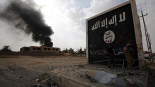 Des combattants irakiens posant devant un symbole de l'Etat islamique.