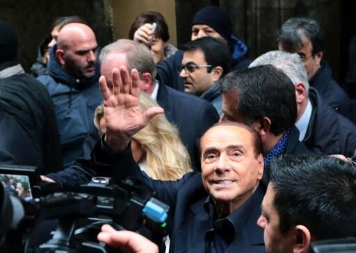 O líder do partido Força Itália, Silvio Berlusconi, acena para a população nas ruas de Nápoles, neste sábado (3).
