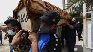 Familiares carregam caixão de vítima de incêndio em hospital para contaminados pela Covid-19 em Bagdá, Iraque.