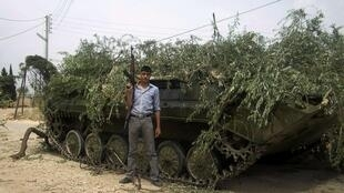 A Syrian rebel fighter poses in front of a captured Syrian army tank