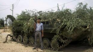 Membro do exército rebelde sírio posa em frente a tanque confiscado das forças de Bashar al-Assad em foto desta terça-feira.