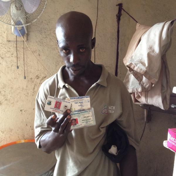 John Namwé, montre des photos de ses proches tués par Ebola.
