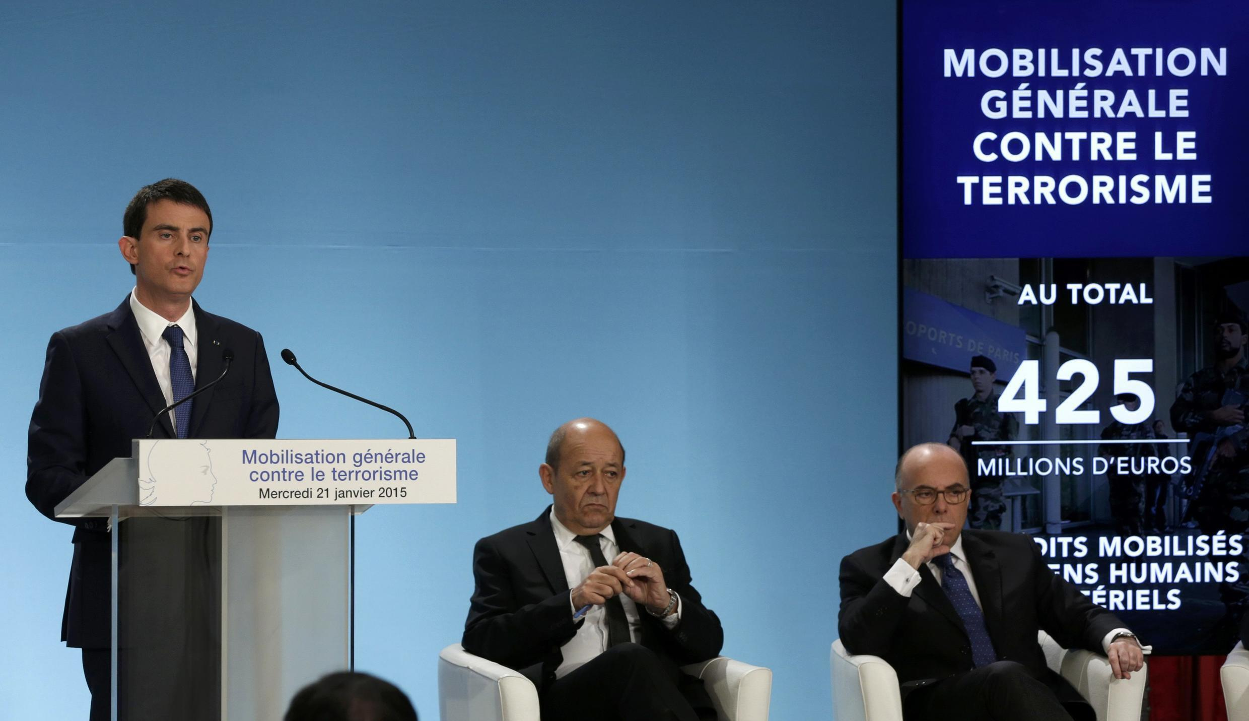 French Defence Minister Jean-Yves Le Drian (C) and Interior Minister Bernard Cazeneuve (R) listen as Prime Minister Manuel Valls outlines his plans to tackle jihadist violence