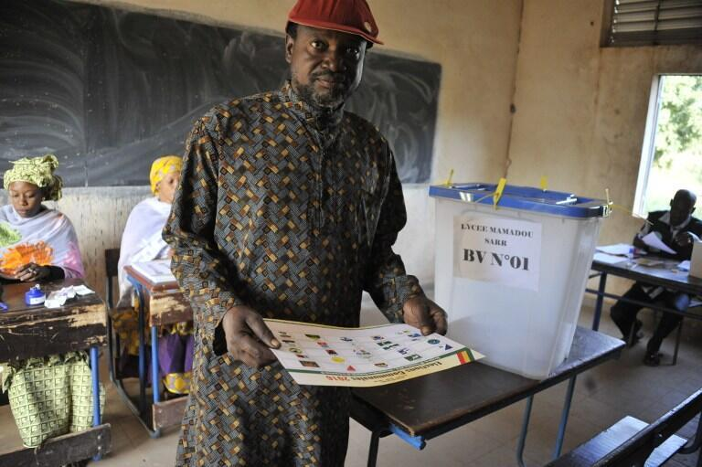 A man holds his ballot paper at a polling station in Bamako on 20 November 2016.