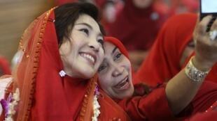 Yingluck Shinawatra (G), la candidate favorite de l'opposition thaïlandaise, et sœur de l'ancien Premeir ministre Thaksin Shinawatra, le 14 juin 2011.