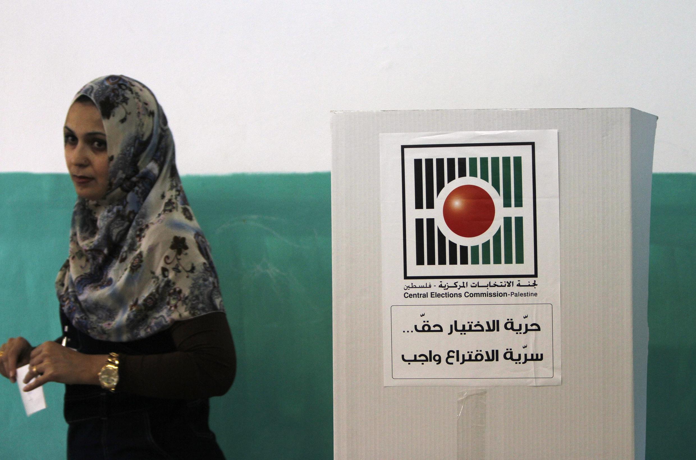 Mulher vota em seção eleitoral em Ramallah, na Cisjordânia, neste sábado (20).