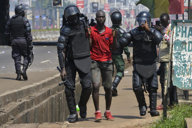 Des policiers arrêtent un homme en marge d'une manifestation à Conakry, Guinée, le 14 novembre 2019.