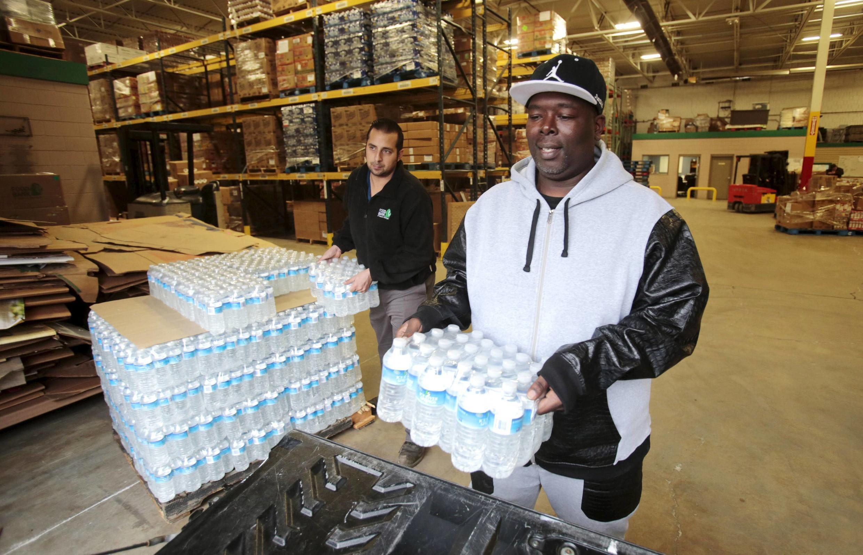 Un residente de Flint, en el estado de Michigan, recupera botellas de agua para entregarlas a una escuela y evitar que los niños beban el agua contaminada de la ciudad.