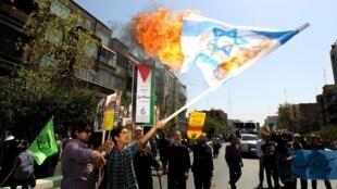 Iranian demonstrators burn an Israeli flag on al-Quds Day in Tehran