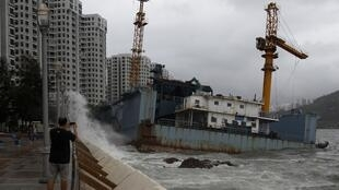 A man takes a picture of a cargo barge after it ran aground in Hong Kong 29 September, 2011