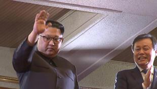 Cette photo capture d'écran d'une vidéo montre le dirigeant nord-coréen Kim Jong-un aux côtés du ministre sud-coréen de la Culture, Sports et Tourisme Do Jong-whan (d) pendant le concert des musiciens sud-coréens, à Pyongyang, le 1er avril 2018.