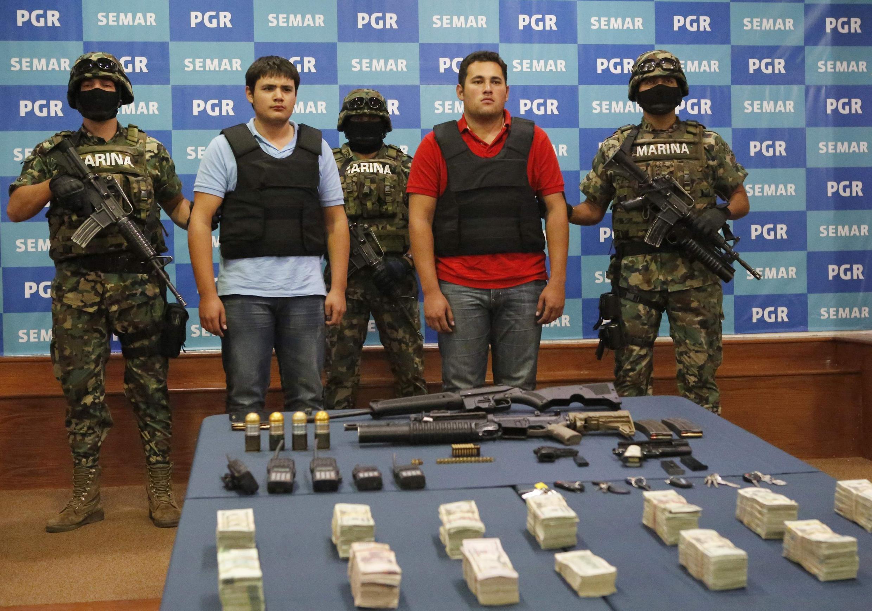 """Soldados mexicanos flanquean a dos hombres implicados en el narcotráfico; uno de ellos es Jesús Alfredo Guzmán, presumiblemente hijo del rey de la cocaina, Joaquíin """"Shorty"""" Guzmán, México, 21 de junio de 2011."""