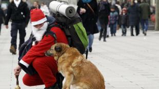 Um morador de rua vestido de Papai Noel na avenida Champs-Elysées, em Paris.