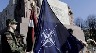 Cờ NATO (P) và quốc kỳ Latvia bên cạnh nhau tại Riga ngày 29/03/2014 nhân lễ kỷ niệm 10 năm ngày Latvia gia nhập NATO.
