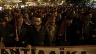 Militantes da coalizão comunista Pame protestam contra cortes no orçamento de 2013, na noite deste domingo, em Atenas.