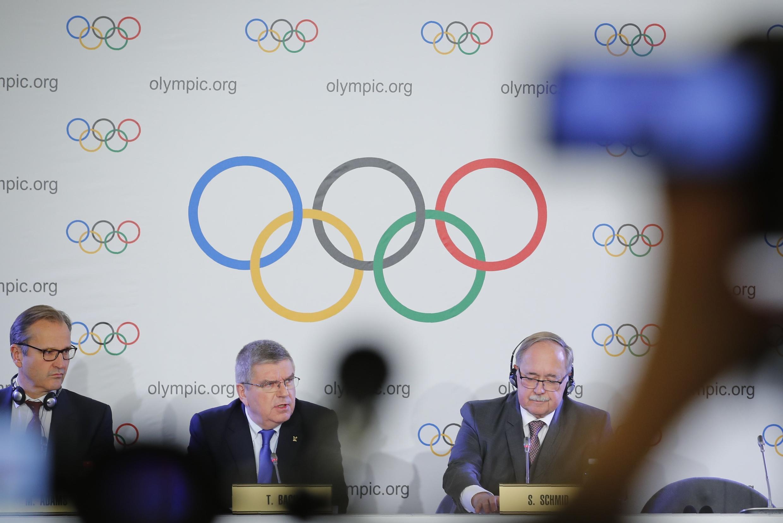 Директор МОК по коммуникациям Марк Адамс, глава комиссии МОК по расследованию допингового скандала Самуэль Шмид и глава МОК Томас Бах на пресс-конференции в Лозанне, 5 декабря 2017.