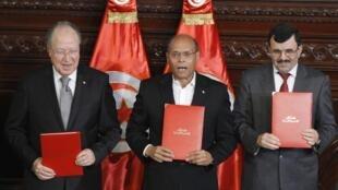 A Tunísia adotou nesta segunda-feira uma nova Constituição.O Presidente da Assembleia Nacional, Mustapha Ben Jaafar, o Presidente da Tunísia, Moncef Marzouki, e o primeiro-ministro, Ali Larayedh, posam para a fotografia.