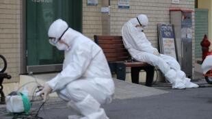 Des membres du personnel médical attendent les ambulances qui transportent des malades contaminés par le coronavirus Covid-19, à l'entrée de l'hôpital de Daegu, le 23 février 2020. Au moins 602 cas confirmés et 5 morts en Corée du Sud.