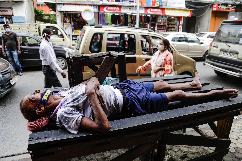 Wani mutum dake barci a gefenn hanya sanye da takunkumin rufe baki da hanci a birnin Kolkata na kasar India.
