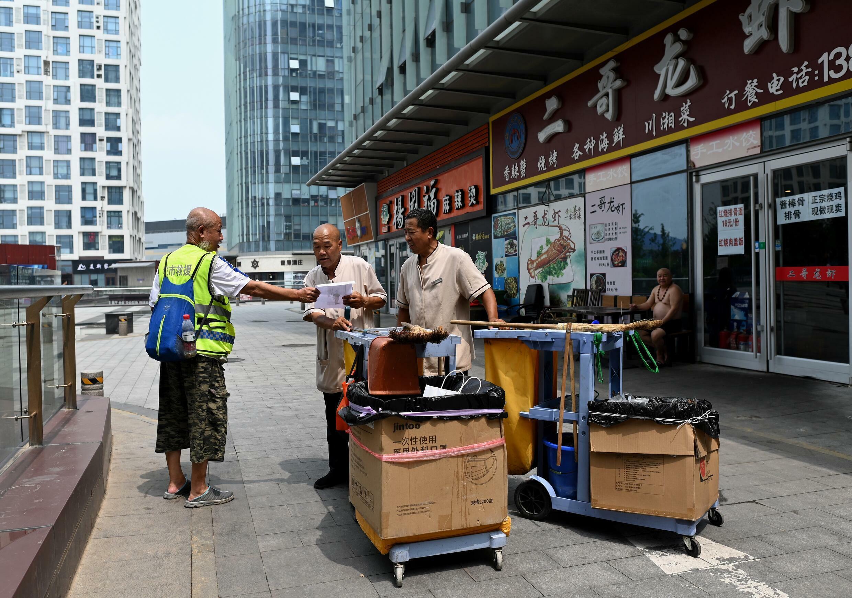 Voluntarios buscan a un enfermo de Alzheimer desaparecido, en Pekín, el 19 de julio de 2021