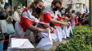 Manifestantes atan aviones de papel a una cuerda durante una manifestación de bielorrusos que viven en Polonia y polacos que los apoyan frente a la oficina de la Comisión Europea para exigir la libertad del activista de la oposición bielorrusa Roman Protasevich en Varsovia, el 24 de mayo de 2021