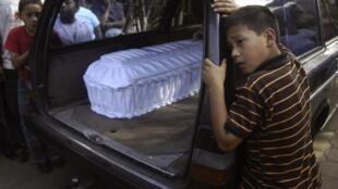 Niños lloran junto a la carroza fúnebre que transporta los ataúdes de las víctimas de una explosión de bus en Ciudad de Guatemala, crimen que fue adjudicado a las maras.