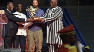 Alain Gomis (centre) reçoit son prix des mains des présidents ivoirien et burkinabè, le 4 mars 2017.