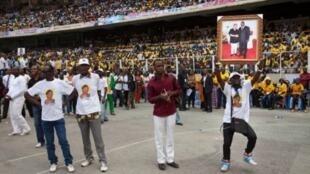 Un membre du Parti du peuple pour la reconstruction et la démocratie (PPRD) brandit le portrait  de Joseph Kabila et de son épouse dans le stade des Martyrs de Kinshasa, le 21 août 2011.