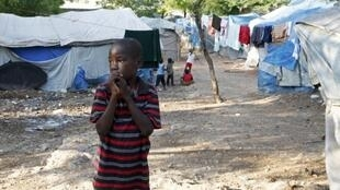 A boy from a family made homeless by the 2010 earthquake stands inside Shelter Camp 3 in the Delmas suburb of Port-au-Prince, 18 April, 2013