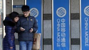 Chineses usam iPhone em frente a banner da China Mobile em Pequim, nesta segunda-feira, 23 de dezembro.